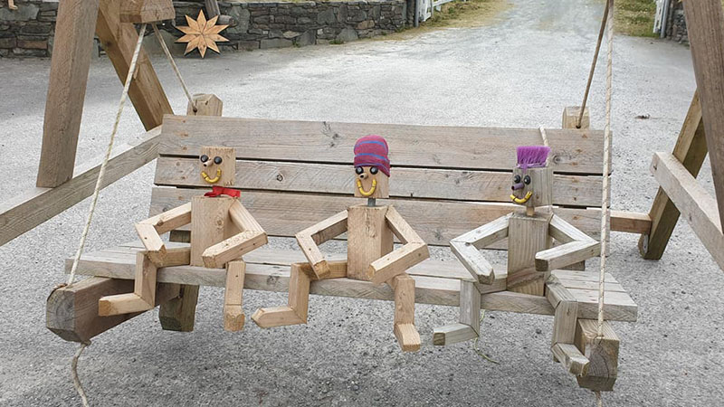 Three wooden amigos swinging on a bench near Macroom