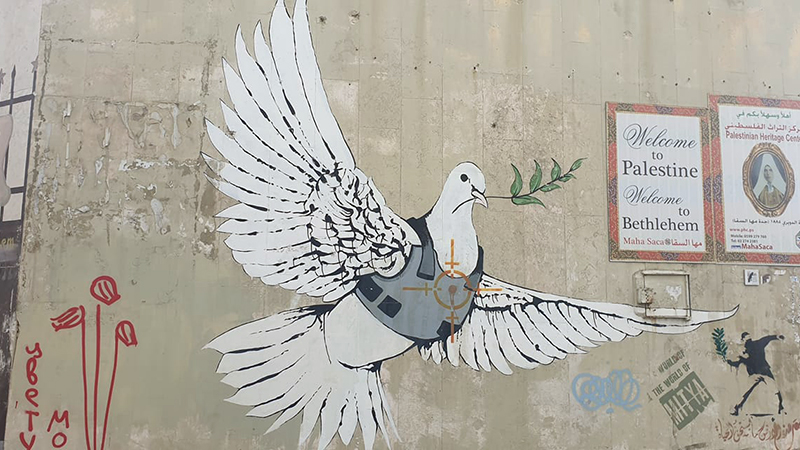 Banksy's dove of peace, sporting a target and a flack jacket, on the Bethlehem Wall. One of the elusive street artist's most iconic works